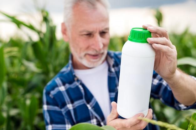 Der alte mann auf einem gebiet, das auf einer flasche in seinen händen schaut. modell der düngerflasche Premium Fotos