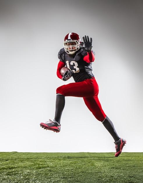 Der amerikanische fußballspieler in aktion auf grünem gras und grauem hintergrund. Kostenlose Fotos