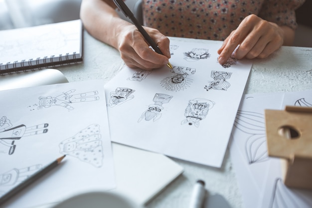 Der animator-designer zeichnet skizzen verschiedener charaktere. Premium Fotos