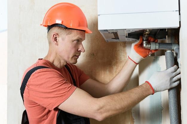 Der arbeiter installiert die gaskesselrohre Premium Fotos