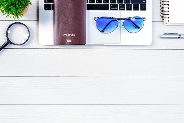 Der arbeitskraft- und angestelltenschreibtisch hat die reise zu träumen und sich vorzubereiten, mit laptop und pass auf weißer hölzerner tabelle von der draufsicht der flachen lage um die welt zu reisen und zu reisen. Premium Fotos