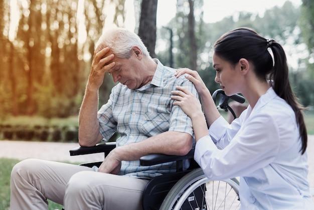 Der arzt beruhigt den niedergeschlagenen alten mann im rollstuhl Premium Fotos