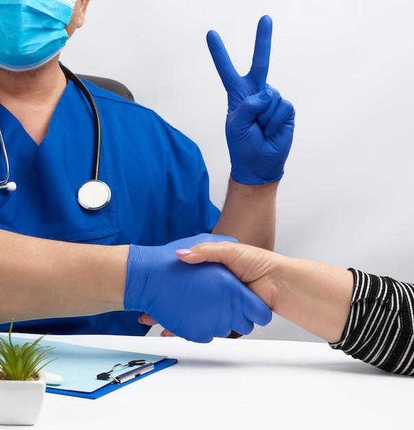 Der arzt in blauer uniform sitzt an einem schreibtisch in einem sessel und gibt einer patientin die hand Premium Fotos