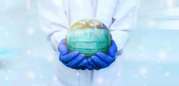 Der arzt trägt handschuhe und hält die erdmaske, um sich vor viren zu schützen Premium Fotos