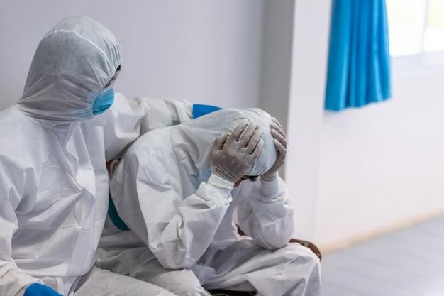 Der arzt tröstet einen kollegen im stress der arbeit in psa-anzuguniform hat stress bei coronavirus-ausbruch oder covid-19 Premium Fotos