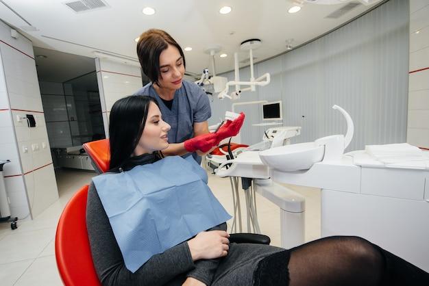 Der arzt zeigt einen abguss des kiefers des patienten. zahnheilkunde Premium Fotos