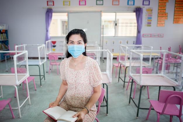 Der asiatische lehrer trägt eine maske im klassenzimmer und in der schule, die kurz vor dem start steht Premium Fotos