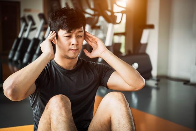 Der asiatische sportmann, der krise tut oder sitzen oben haltung auf yogamatte in der eignungsturnhalle Premium Fotos