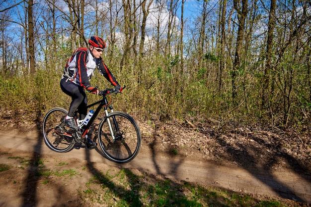 Der athlet fährt mit dem fahrrad auf unwegsamkeit im wald. Premium Fotos