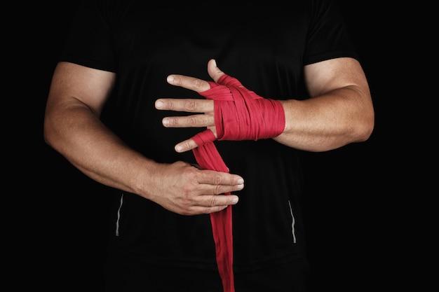 Der athlet steht in schwarzer kleidung und umwickelt seine hände vor dem training mit einem roten textilverband Premium Fotos