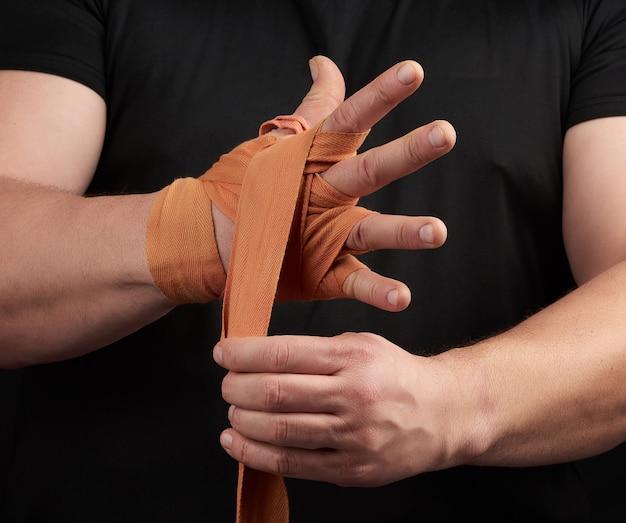 Der athlet steht in schwarzer kleidung und wickelt seine hände in einen roten elastischen orangefarbenen textilverband Premium Fotos