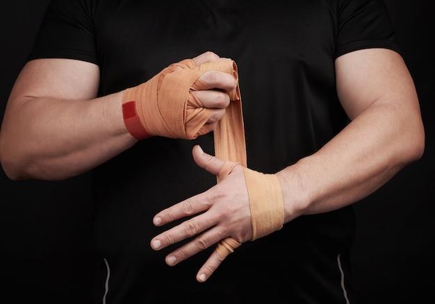 Der athlet steht in schwarzer kleidung und wickelt seine hände in einen roten elastischen textilverband Premium Fotos