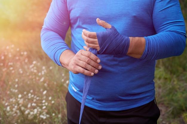 Der athlet steht und umwickelt seine hände mit einem blauen textilverband Premium Fotos