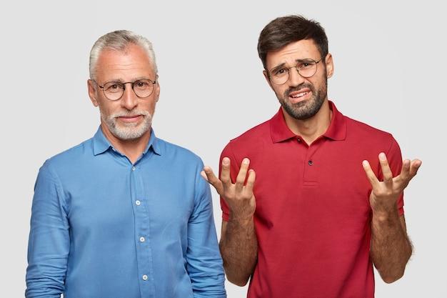 Der attraktive männliche rentner arbeitet mit seinem jungen kollegen zusammen, der verzweifelt nervös ist und nebeneinander steht, isoliert über einer weißen mauer. menschen und beziehungen Kostenlose Fotos