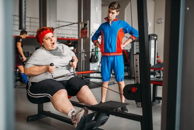 Der ausbilder zwingt die dicke frau, an einem trainingsgerät zu arbeiten, ein hartes training im fitnessstudio. Premium Fotos