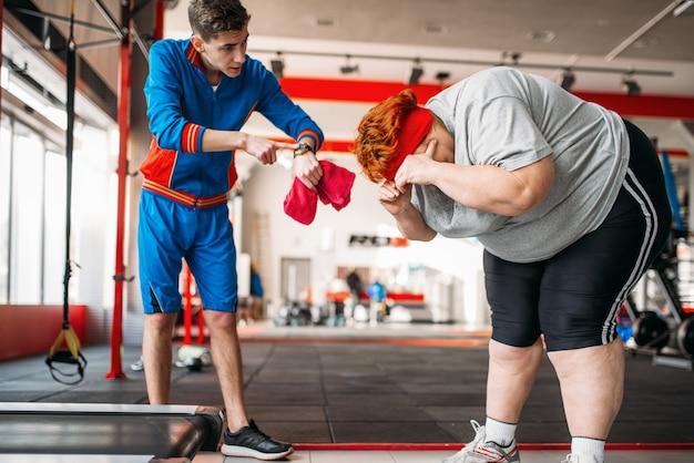 Der ausbilder zwingt die dicke frau, im fitnessstudio hart zu trainieren. Premium Fotos