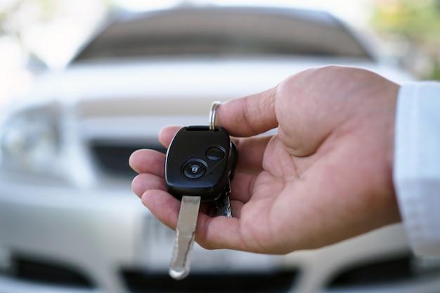 Der autobesitzer hält dem käufer die autoschlüssel bereit. Premium Fotos
