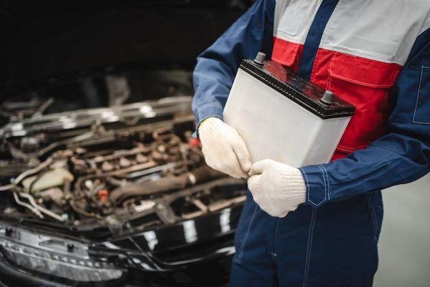 Der automechaniker ist dabei, eine neue batterie für die kunden auszutauschen, die den batteriewechselservice im geschäft nutzen. Premium Fotos