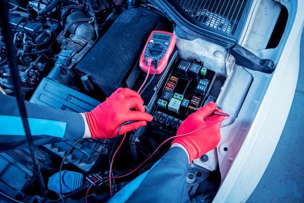 Der automechaniker überprüft den spannungspegel mit einem voltmeter. Premium Fotos
