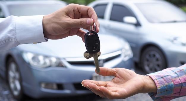 Der autoverkäufer schickte die schlüssel an den neuen autobesitzer Premium Fotos