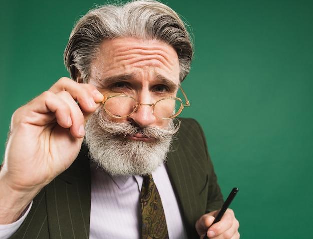 Der bärtige und schnurrbärtige lehrer mittleren alters im anzug hält die hand mit der brille und schaut auf eine grüne wand Premium Fotos