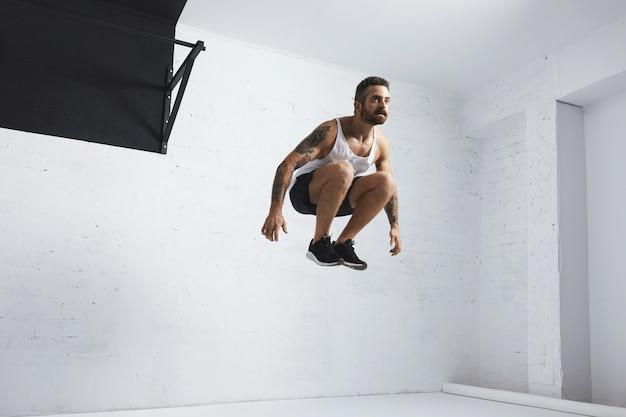 Der bärtige und tätowierte junge männliche athlet zeigt calisthenic-bewegungen, springt hoch in die luft neben der schwarzen zugstange und trägt ein leeres tank-t-shirt, das im weißen raum des fitnesscenters isoliert ist Kostenlose Fotos