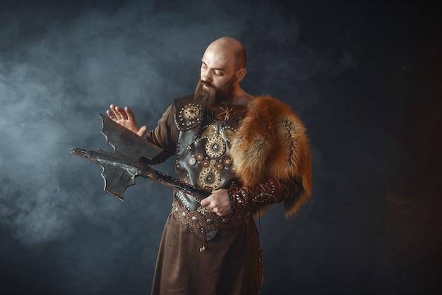 Der bärtige wikinger in traditioneller nordischer kleidung berührt die axtklinge Premium Fotos