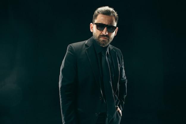Der barde im anzug. stilvoller geschäftsmann auf schwarzem studio Kostenlose Fotos