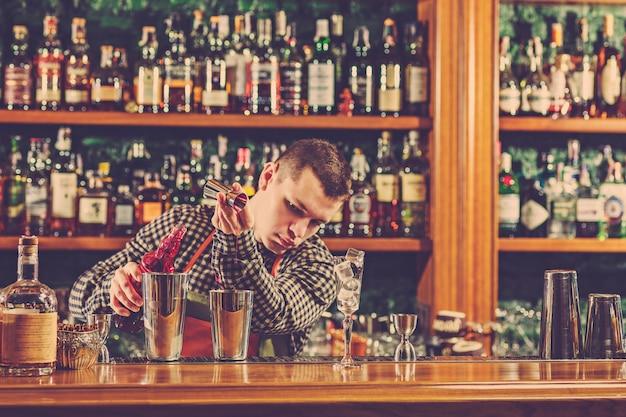 Der barmann macht einen alkoholischen cocktail an der theke in der bar Kostenlose Fotos