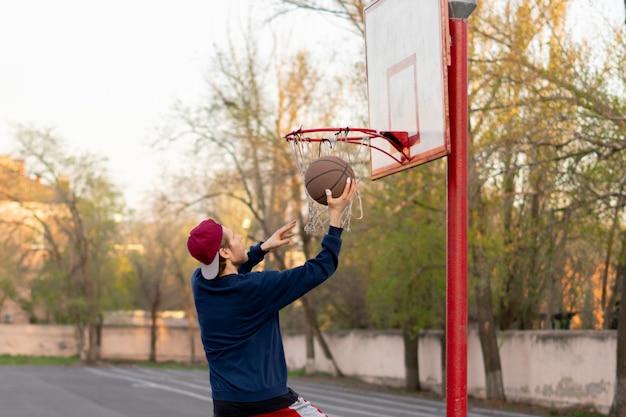Der basketball-spieler, der das übungsschießen tut, bohrt im freien in den stadtstraßengerichten Premium Fotos
