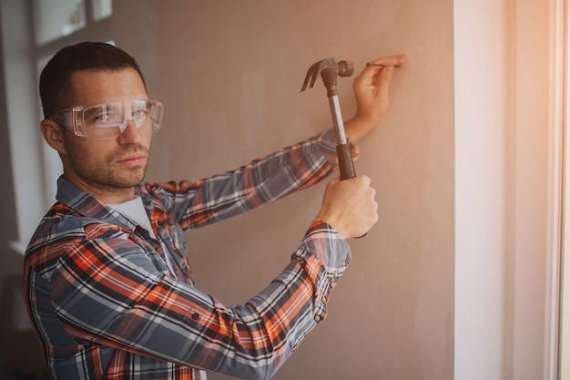 Der bauherr arbeitet auf der baustelle. arbeiter mit eimer und farbroller in der nähe der wand. Premium Fotos