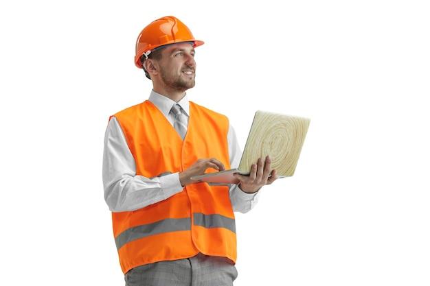 Der baumeister in einer bauweste und einem orangefarbenen helm mit laptop. sicherheitsspezialist, ingenieur, industrie, architektur, manager, beruf, geschäftsmann, jobkonzept Kostenlose Fotos