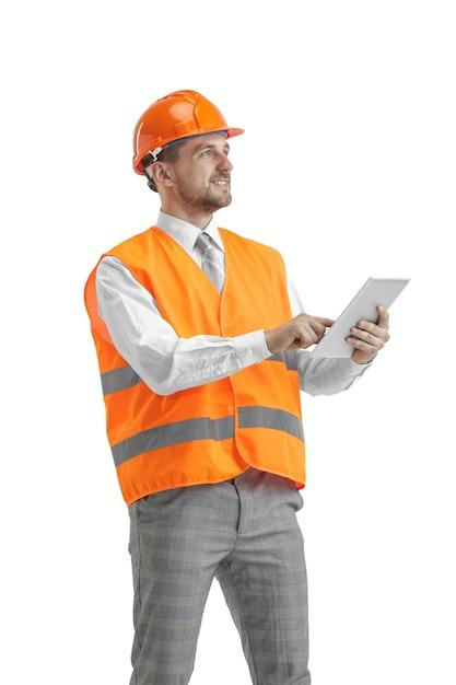 Der baumeister in einer bauweste und einem orangefarbenen helm mit tablette. sicherheitsspezialist, ingenieur, industrie, architektur, manager, beruf, geschäftsmann, jobkonzept Kostenlose Fotos