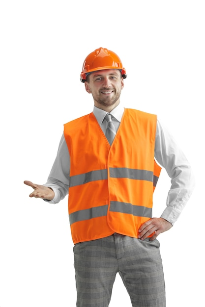 Der baumeister in einer bauweste und einem orangefarbenen helm steht auf weißer wand. sicherheitsspezialist, ingenieur, industrie, architektur, manager, beruf, geschäftsmann, jobkonzept Kostenlose Fotos