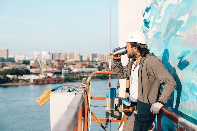 Der bauunternehmer, ein künstler in großer höhe in einer gebäudewiege, machte eine arbeitspause und trank kaffee aus einem thermocup Premium Fotos