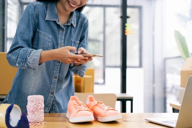 Der besitzer eines online-verkäufers macht ein foto des produkts, um es in den online-shop der website hochzuladen. Premium Fotos
