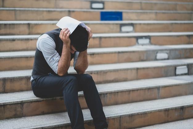 Der betonte geschäftsmann, der kündigung vertrag hält, setzte an seinen kopf beim sitzen auf der treppe Premium Fotos