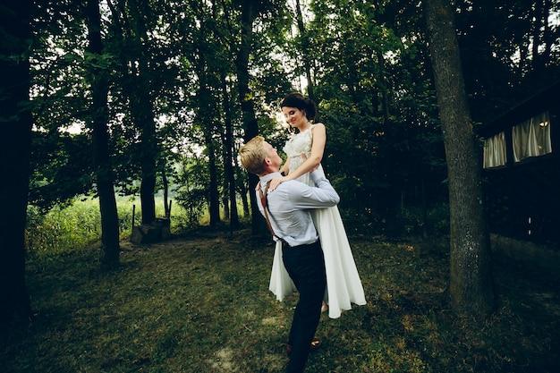 Der bräutigam hob die braut im park in die arme Kostenlose Fotos