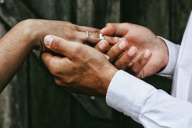 Der bräutigam legt den ring auf den arm seiner verlobten Premium Fotos