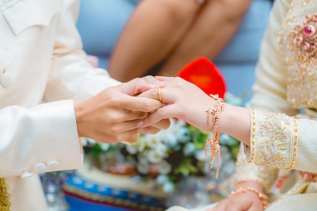 Der bräutigam trägt den ehering zum finger der braut Premium Fotos