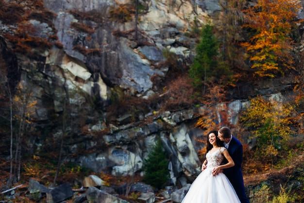 Der bräutigam umarmt die braut von hinten und sie lächeln. Premium Fotos
