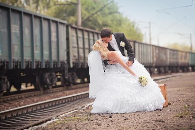 Der bräutigam und die braut mit einem koffer am bahnhof Premium Fotos