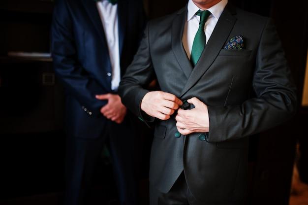 Der bräutigam verkleidet sich in gegenwart seiner trauzeugen im zimmer. Premium Fotos