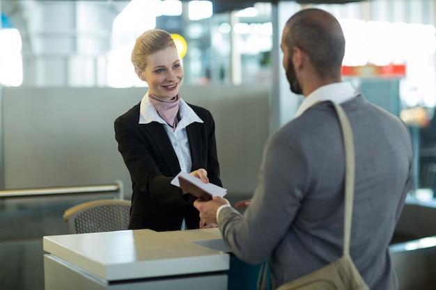 Der check-in-mitarbeiter der fluggesellschaft übergibt dem pendler den reisepass Kostenlose Fotos