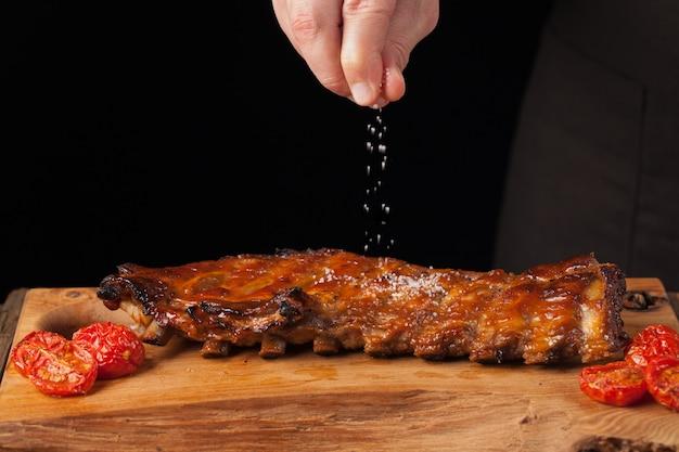 Der chef besprüht salz in verzehrfertigen schweinerippchen. Premium Fotos