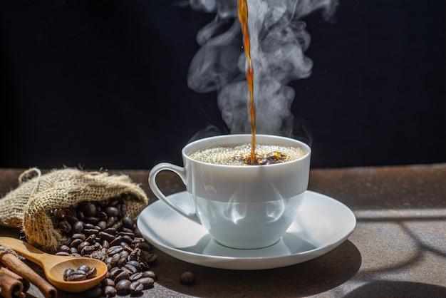 Der dampf vom eingießen des kaffees in die tasse, eine tasse frischen kaffees Premium Fotos