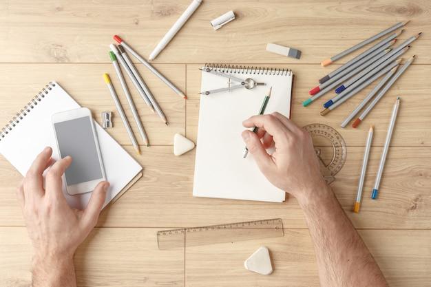 Der designer zeichnet eine skizze in ein notizbuch auf einem holztisch. schreibwaren. von oben betrachten. Premium Fotos