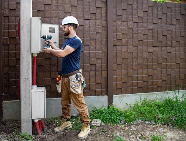 Der elektriker bei der arbeit untersucht die kabelverbindung in der elektrischen leitung im rumpf einer industriellen schalttafel. professionell in overalls mit einem elektrikerwerkzeug. Kostenlose Fotos