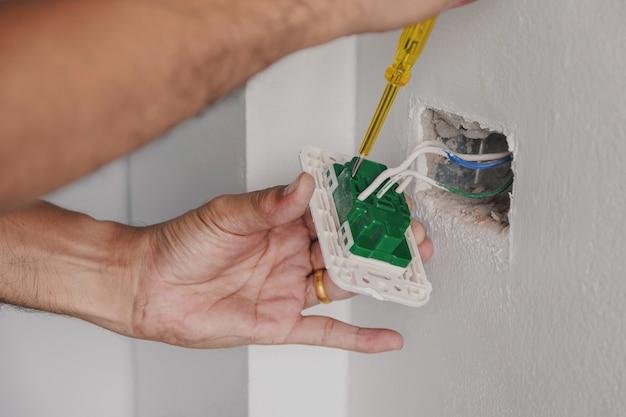 Der elektriker prüft mit einem schraubenzieher den netzstecker an der wand. Premium Fotos