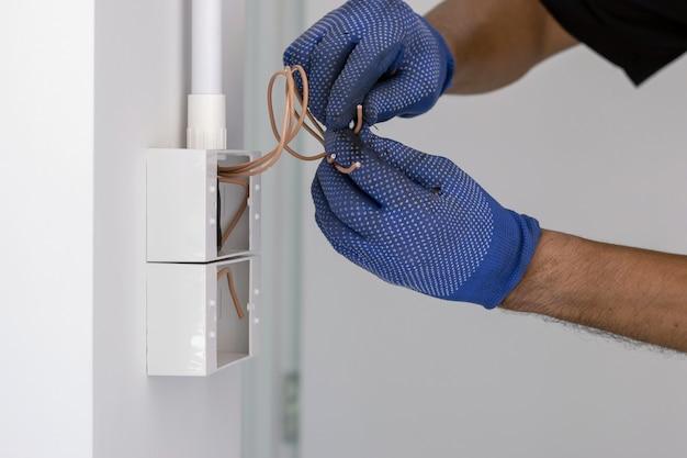Der elektriker trägt blaue handschuhe und verwendet ein elektrisches kabelschneidemesser, um den stecker zu installieren Premium Fotos